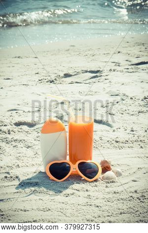 Carrot Juice, Sunglasses And Sun Lotion On Sand At Beach, Concept Of Prevention Of Vitamin A Deficie