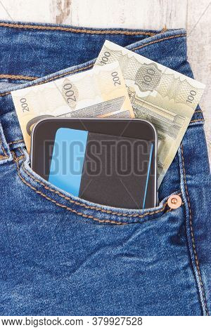 Credit Card, Money And Mobile Phone In Front Jeans Pocket. Concept Of Cashless Or Cash Paying For Sh