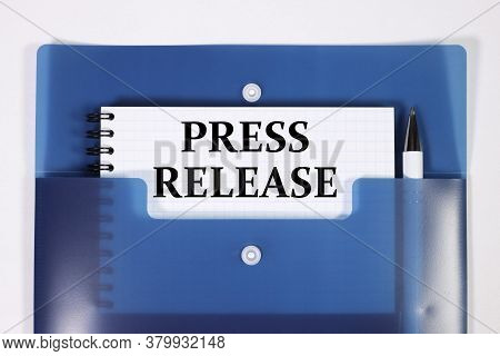 Press Release. Text On White Paper On Blue Background And Pens