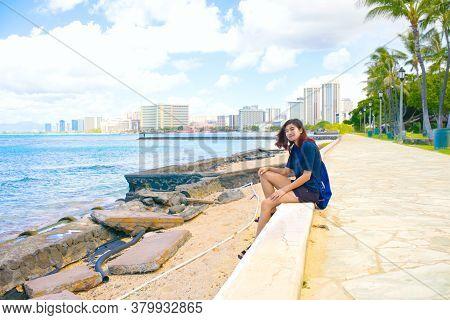 Smiling Biracial Asian Caucasian Young Woman Or Teen Girl Sitting Along Stone Walking Path Along The