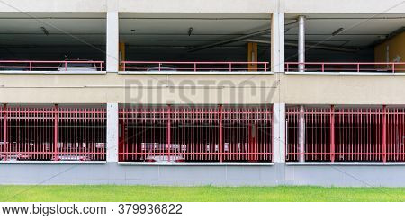 Large Parking Lot Construction Floors With Red Metal Handrails And Green Grass Of Flowerbed On Foreg