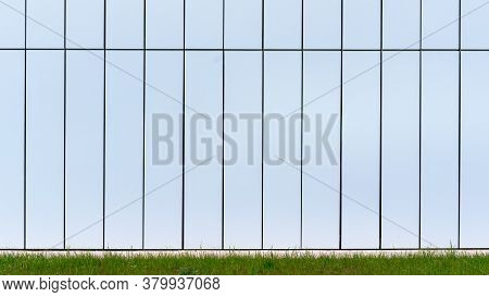 White Building Wall With Black Decorative Lines At Green Grass Of Flowerbed Under Bright Sunlight On