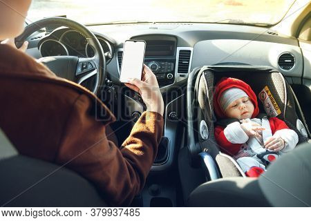 Mom Drives The Car With Phone In Her Hands, While Her Little Child Sits In The Front Baby Car Seat F