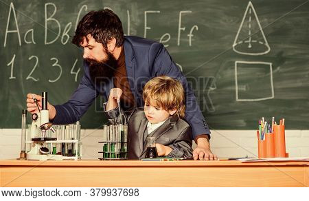 Teacher Man With Little Boy. School Lab Equipment. Student Doing Science Experiments With Microscope