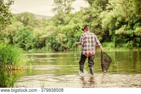 Calling Fly-fishing A Hobby. Fisherman With Fishing Rod. Retired Bearded Fisher. Trout Bait. Hobby A