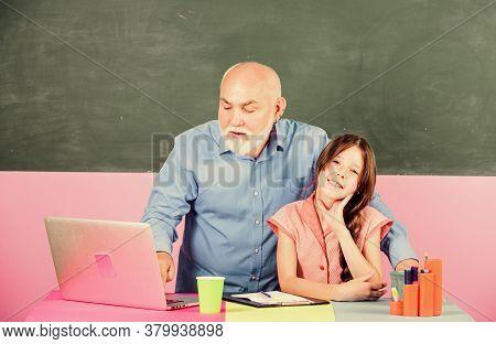 Making Lives Better. Senior Teacher Help School Girl. Small Girl With Man Tutor Study On Laptop. Onl