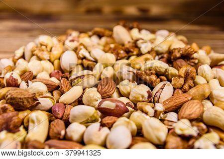 Background Of The Various Nuts (almond, Cashew, Hazelnut, Pistachio, Walnut) Wooden Table. Vegetaria