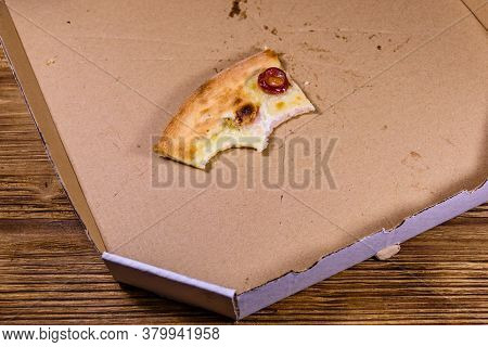 Last Piece Of Pizza With Sausages, Ham And Parmesan Cheese In Cardboard Box