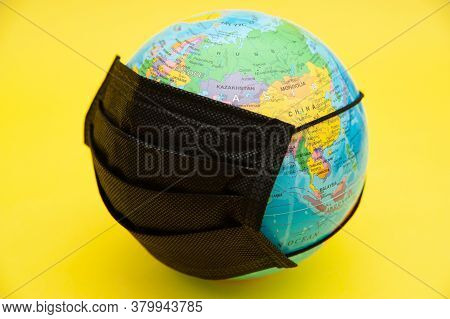Terrestrial Globe Model With Black Surgical Mask Isolated On Yellow Background. Concept: Planet Eart
