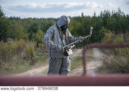 A Military Man In A Chemical Protection Suit Measures Radiation With A Dosimeter Standing In Front O