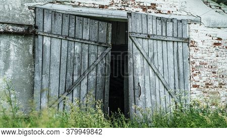Abandoned Village Building Wooden Door And Peeling Brick Walls With Green Grass On Foreground On Nas