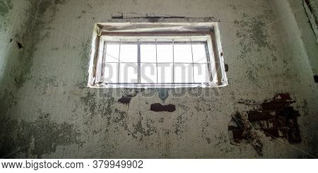 Old Window With Wooden Frame And Metal Grid In Abandoned Shed Building Premises With Dirty Walls Low