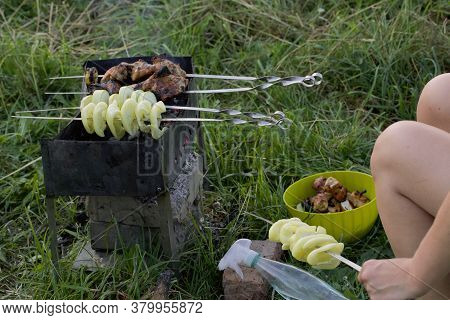A Woman Prepares A Barbecue Of Chicken And Vegetables. Skewers On The Grill. You Can See Fried Chick