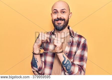 Young handsome man wearing prisoner handcuffs smiling happy pointing with hand and finger