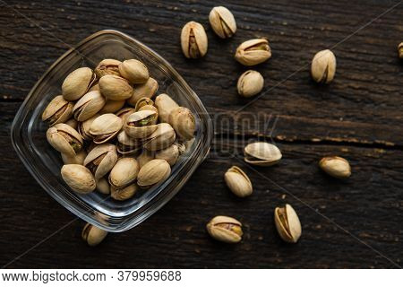 Pistachios In A Small Plate With Scattered Nuts Of Almonds Around A Plate On A Vintage Wooden Table