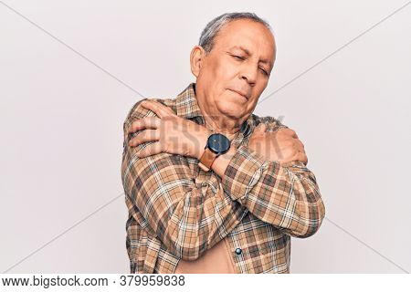 Senior man with grey hair wearing casual shirt hugging oneself happy and positive, smiling confident. self love and self care