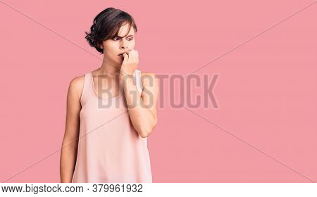 Beautiful young woman with short hair wearing casual style with sleeveless shirt looking stressed and nervous with hands on mouth biting nails. anxiety problem.