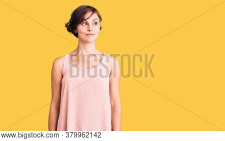 Beautiful young woman with short hair wearing casual style with sleeveless shirt smiling looking to the side and staring away thinking.