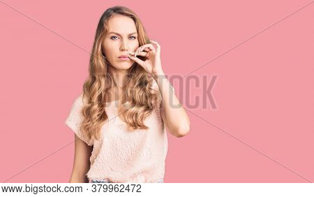 Young beautiful caucasian woman with blond hair wearing casual clothes mouth and lips shut as zip with fingers. secret and silent, taboo talking