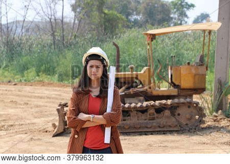 Female Civil Engineer Or Architect With White Helmet Cross One's Arm And Project Drafts While In Han