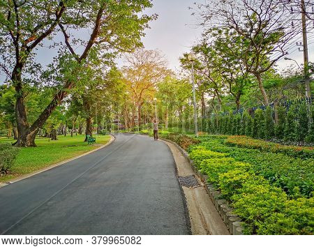 A Black Asfalt Concrete Jogging Track In A Public Park, A Man Walking On Curve Shape Walkway Under E