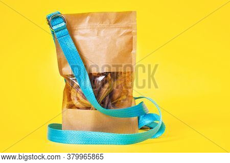 Dog Cloth Leash And Tasty Dried Treats For Pets In Paper Eco Recyclable Bag Are On Yellow Background