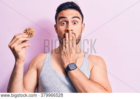 Young handsome man with beard wearing sleeveless t-shirt eating chocolate cookie covering mouth with hand, shocked and afraid for mistake. Surprised expression