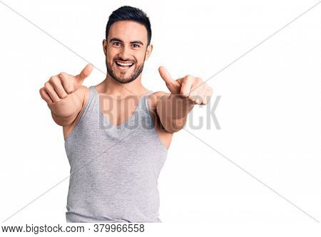 Young handsome man wearing swimwear and sleeveless t-shirt approving doing positive gesture with hand, thumbs up smiling and happy for success. winner gesture.