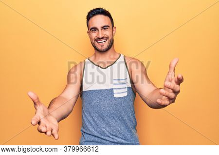 Young handsome man with beard wearing sleeveless t-shirt standing over yellow background looking at the camera smiling with open arms for hug. Cheerful expression embracing happiness.