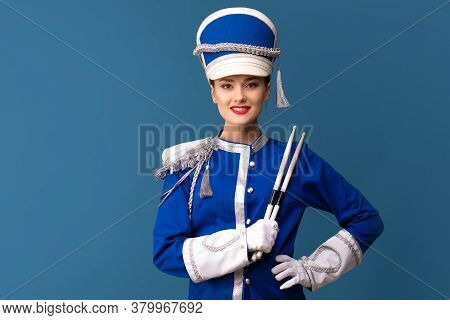 Beautiful Young Woman From The Orchestra. A Drummer In A Blue Uniform With Drumsticks