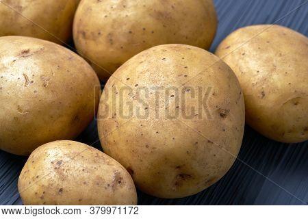 Fresh Raw Potatoes On Textured Background