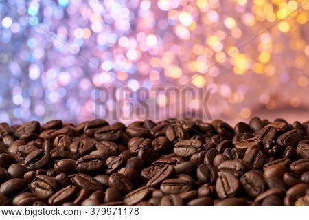 Heap Of Roasted Brown Whole Coffee Beans With A Blurred Red And Blue Background