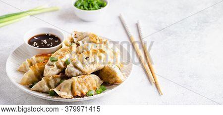 Fried Dumplings Gyoza With Soy Sauce, And Chopsticks.