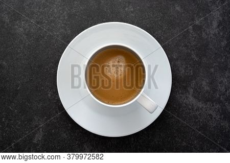 A Flat Lay Top Down Photo Of A White Saucer And Cup Filled With Coffee Placed On Dark Stone Table