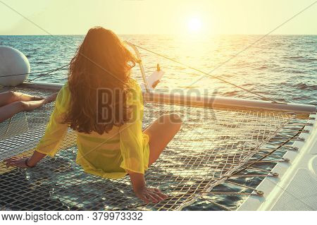 Woman Sits On The Deck Of A Sailing Catamaran At Sunset In The Sun. Rear View Of A Woman Enjoying Th