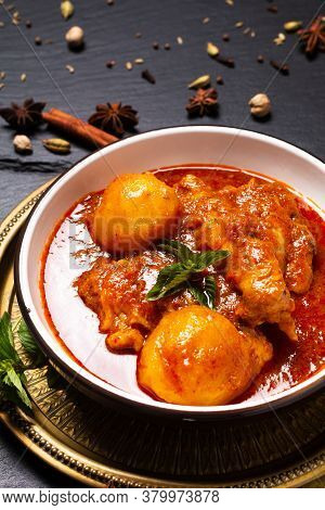 Asian Food Concept Homemade Spicy Chicken Masala Or Thai Massaman Curry With Spices Foreground On Bl