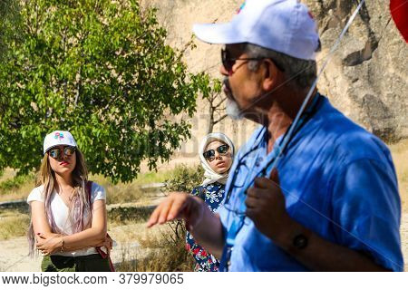 Cappadocia, Turkey April 17, 2019:\na Tour Guide Explaining To Tourists The History Of The Rocks In