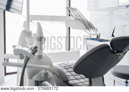 Interior Of Dental Practice Room With Chair, Lamp, Display And Stomatological Tools