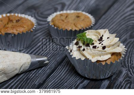 Banana Cupcake. With Butter Cream And Banana Jam. Decorated With Mint Leaves And Chocolate Sprinkles