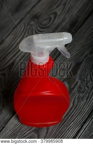 Red Plastic Bottle With Spray. Cleaning Spray. On Painted Pine Planks.