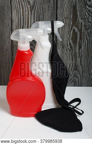 Plastic Bottles Of White And Red Color With A Spray Gun. Cleaning Spray. Next To It Is A Black Face