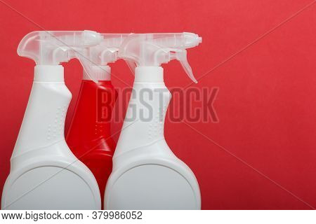 Plastic Bottles Of White And Red Color With A Spray Gun. Cleaning Spray. On A Coral Background.