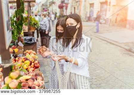 Charming Woman With Teenager Daughter Wearing A Protective Face Mask At An Outdoor Fruit And Veg Mar