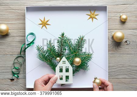 Christmas Decorations, Flat Lay With Hands Making Decorated Box With House Silhouette, Fir Twigs And