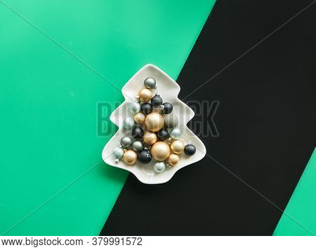 Various Xmas Baubles In Fir Shaped Plate On Layered Diagonal Green And Black Paper, Trendy Minimalis