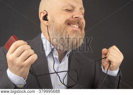 Bearded Business Man Enjoys Listening To His Favorite Music Through An Audio Player In Small Headpho