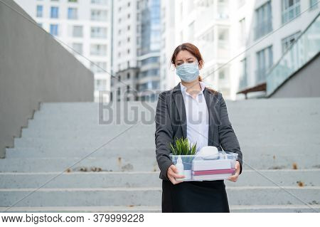 Unhappy Fired Masked Woman Is Standing In The Street With A Box Of Personal Items From The Desktop.