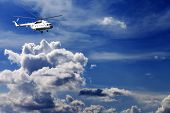 Helicopter in blue sky with clouds in sunny day poster