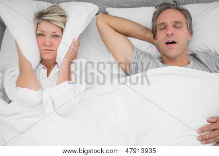 Man snoring loudly as partner blocks her ears at home in bedroom