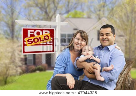 Happy Mixed Race Young Family in Front of Sold Home For Sale Real Estate Sign and House.